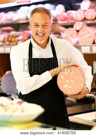Shopkeeper showing mortadella in an italian grocery store