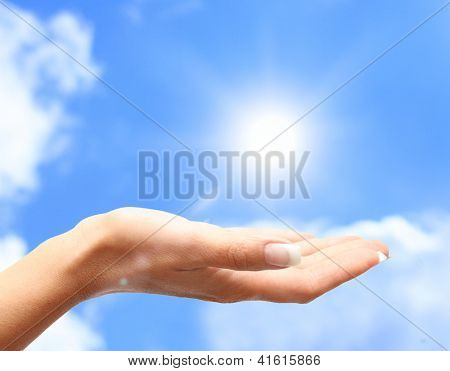 Sun on human hand against blue sky.