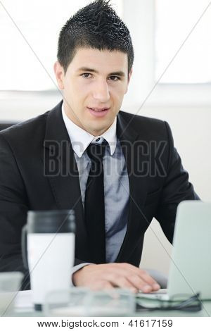 Young businessman working in office using laptop