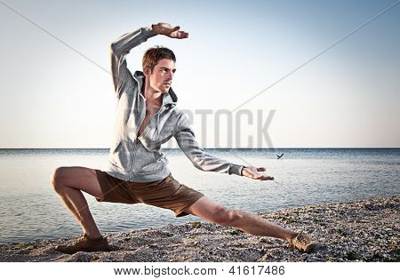 Young attractive man making Thai-chi movements on the beach of Black sea
