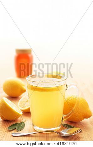 Hot lemon drink in a glass mug on wood with honey, lemons and sage leaves