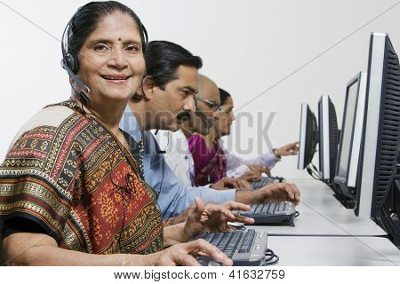 Portrait of a senior female customer service operator in sari with colleagues at office
