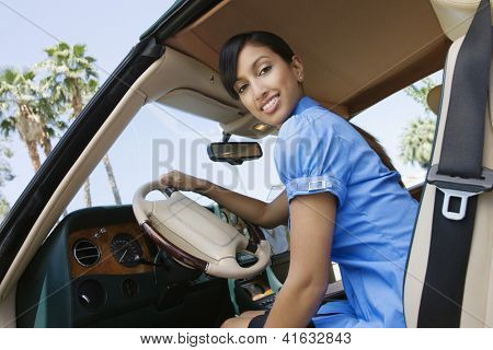 Low angle view of young Indian business woman in car holding steering wheel