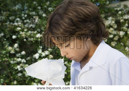 Closeup of a preadolescent boy sneezing in lawn