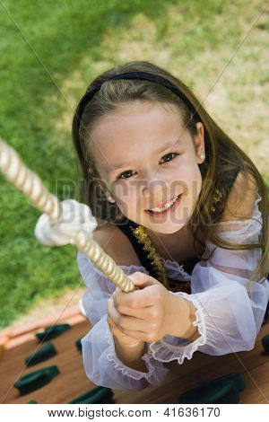 Portrait of a happy preadolescent girl hanging on a rope