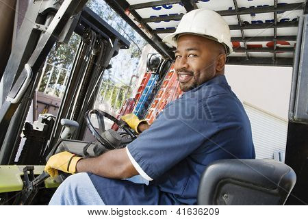 Portrait of a happy African American  male worker driving forklift at workplace
