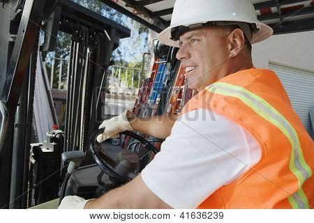 A happy industrial worker driving forklift at workplace