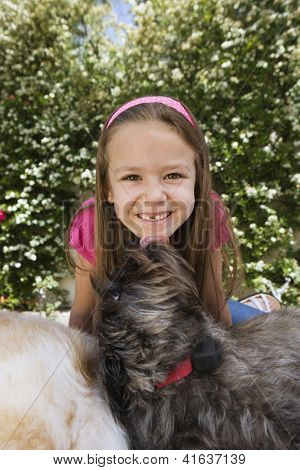 Portrait of a happy cute preadolescent girl with two pet dogs in the garden