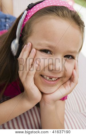 Portrait of a happy cute preadolescent girl listening to music