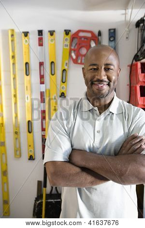Portrait of a happy African American male standing against measuring instruments hanging on wall