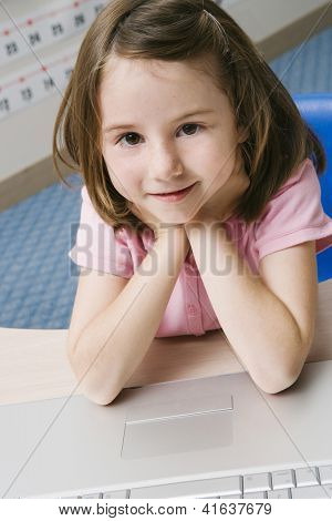 Portrait of a cute preadolescent girl sitting with laptop in the classroom