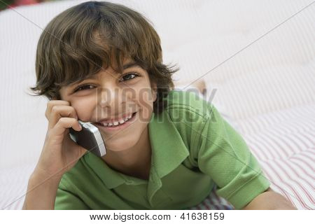 Portrait of a preadolescent boy holding cell phone while lying on bed