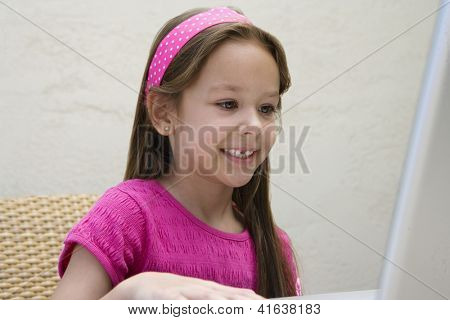 Cute little preadolescent girl using laptop