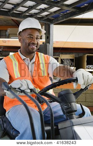 A happy African American male industrial worker driving forklift at workplace