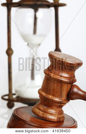 Gavel and block, with antique hourglass behind.