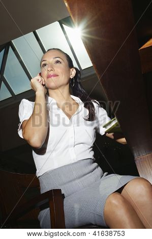 Low angle view of a beautiful business woman talking on mobile phone while sitting on chair at office