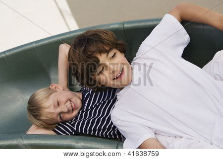 Two preadolescent happy boys enjoying themselves on slide