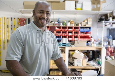 Portrait of happy African American male architect standing at workplace