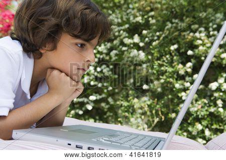 Preadolescent boy looking at laptop