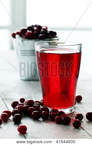 Cranberry juice and berries on a wooden surface