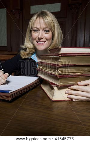 Portrait of a happy female advocate sitting with books and writing notes