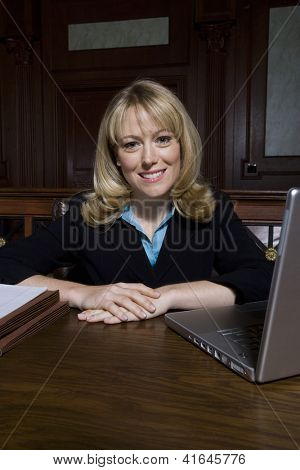 Portrait of a happy female advocate sitting in courtroom