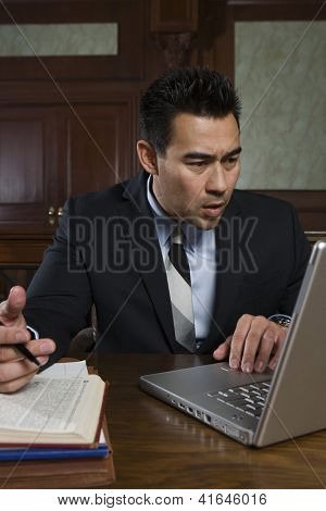 Young male advocate using laptop at courtroom