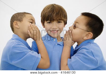 Portrait of little boy smiling while his friends share secret with him over white background