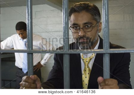 Portrait of a middle aged businessman behind prison gate holding bars