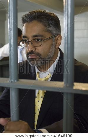 Middle aged businessman in jail with colleague in the background