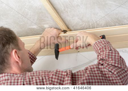 Contractor installing wood panels on a ceiling