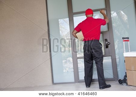 Rear view of a delivery man with packages knocking at door