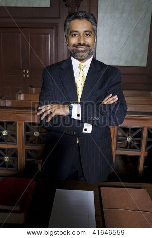 Portrait of a happy advocate standing with hands folded in courthouse