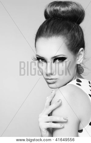 Black and white portrait of young beautiful girl with fancy cat eyes and big retro hair bun
