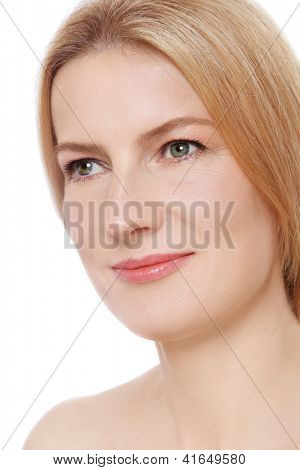 Close-up portrait of beautiful mature woman with clear skin looking upwards, on white background