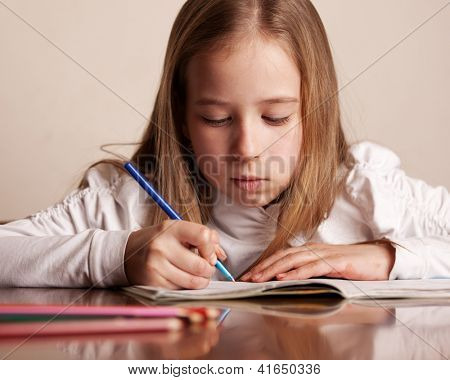 Child doing homework. Sad girl writing