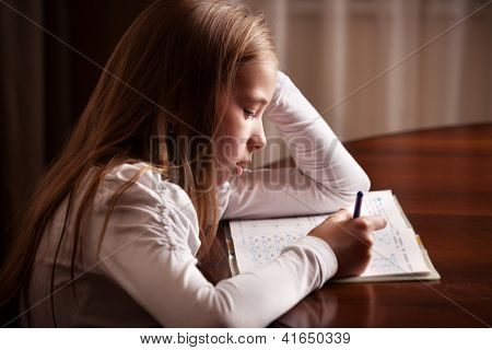 Child doing homework. Sad girl writing, reading
