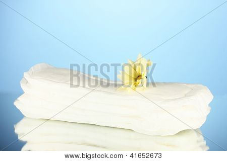 Panty liners and yellow flower on blue background close-up