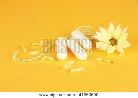 cotton tampons with yellow flower on orange background close-up