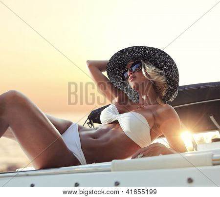 Young sexy woman in white bikini enjoying the sunset on her private yacht