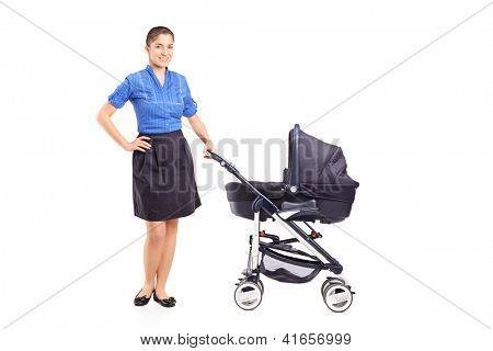 Voller Länge Portrait einer jungen Mutter posiert neben einem Sportkinderwagen, isolated on white background