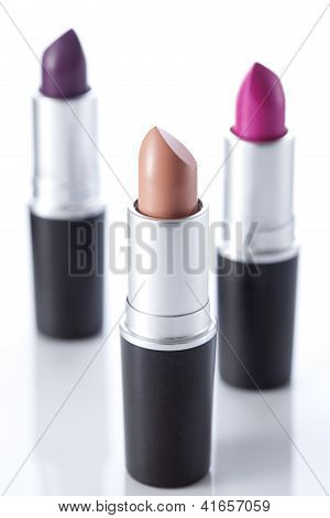 Three color lipsticks on white background