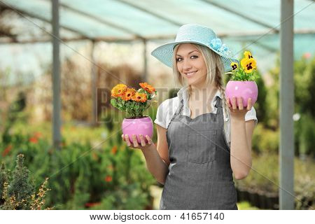 Young female gardener holding flower pots in a garden