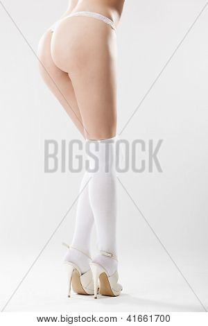Bum and legs of slim sexy woman in stilettos over white background