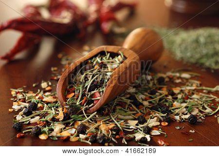 Bodegón de hierbas y especias se derrame de pequeña cucharada madera tablero de corte de madera con pimientos