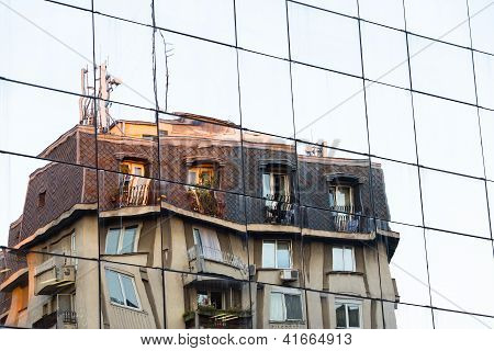Old Building Reflecting On Modern Glass Facade