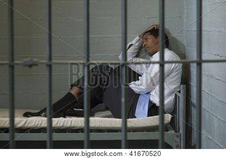Businessman sitting with hand on head behind the bars