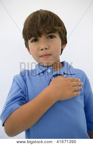 Portrait of little boy in casual t-shirt standing with hand on heart
