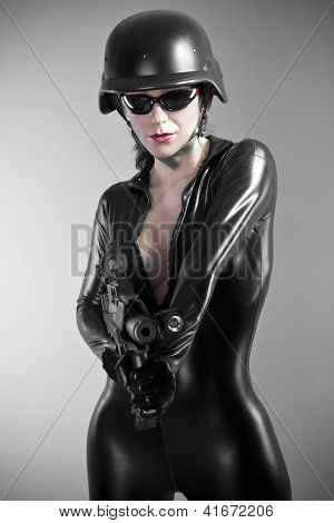 Sexy brunette woman in latex jumpsuit with heavy gun and helmet