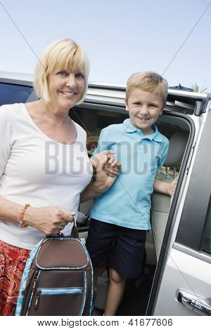 Portrait of mature woman helping grandson get down from minivan while holding his school bag